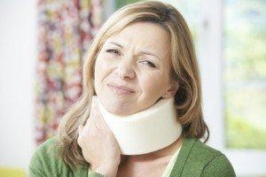 Frau mit Nackenstütze und Schmerzen
