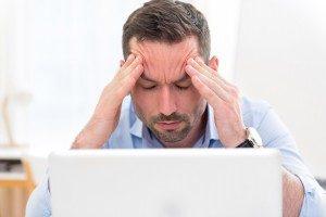 Junger Mann mit Kopfschmerzen am Schreibtisch