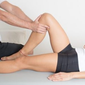 Physotherapeut behandelt Knie einer Frau