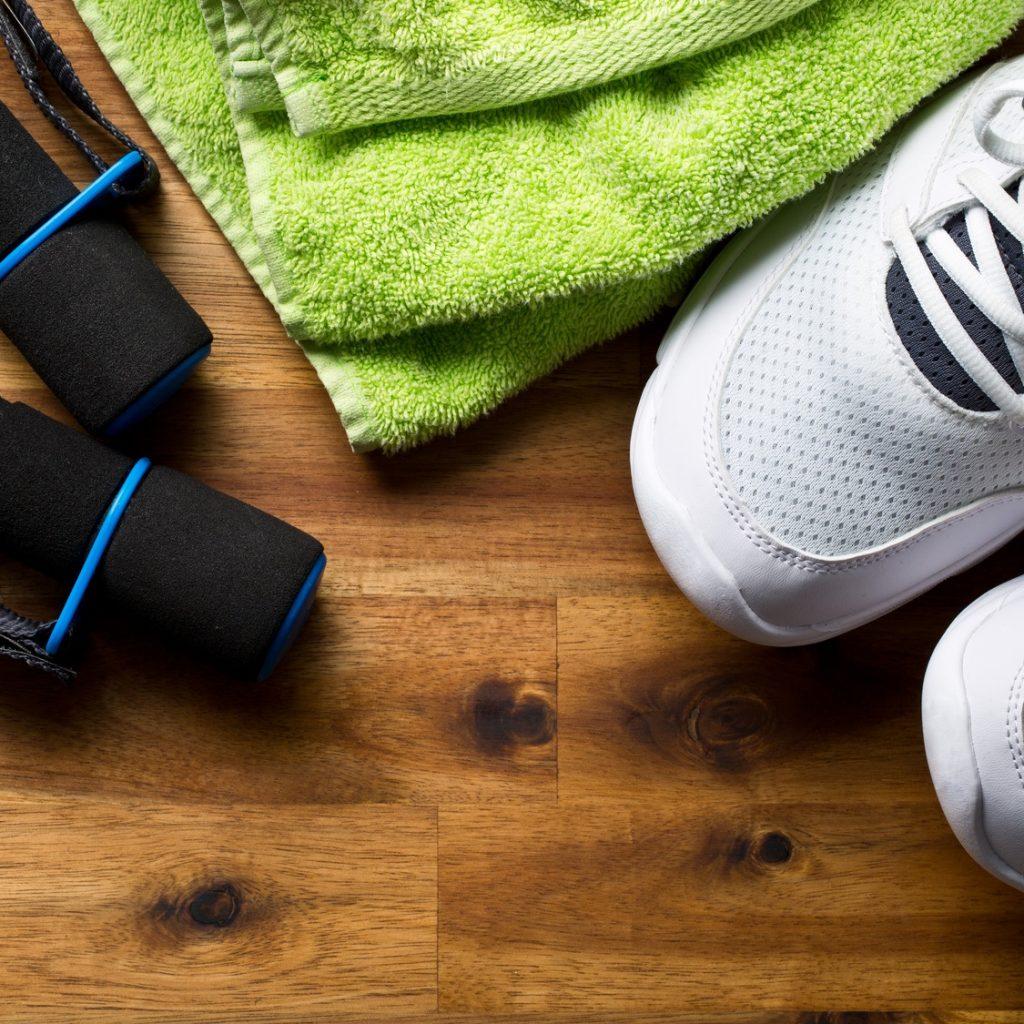 Sportschuhe, grünes Handtuch und kleine Hanteln